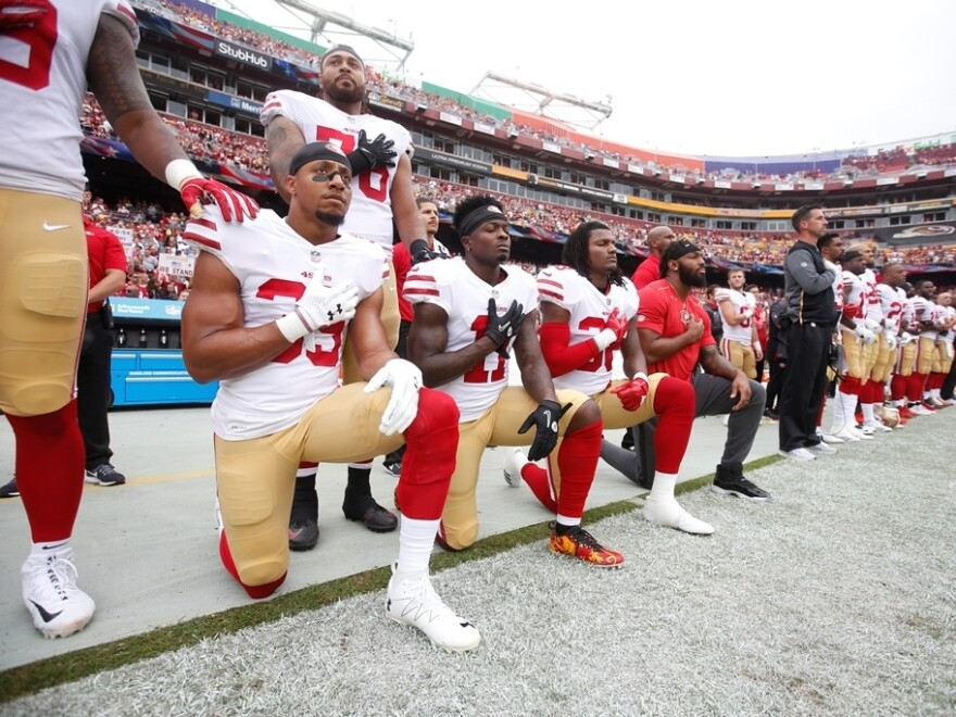 Members of the San Francisco 49ers kneel with teammates during the national anthem before playing the Washington Redskins at FedEx Field in October.