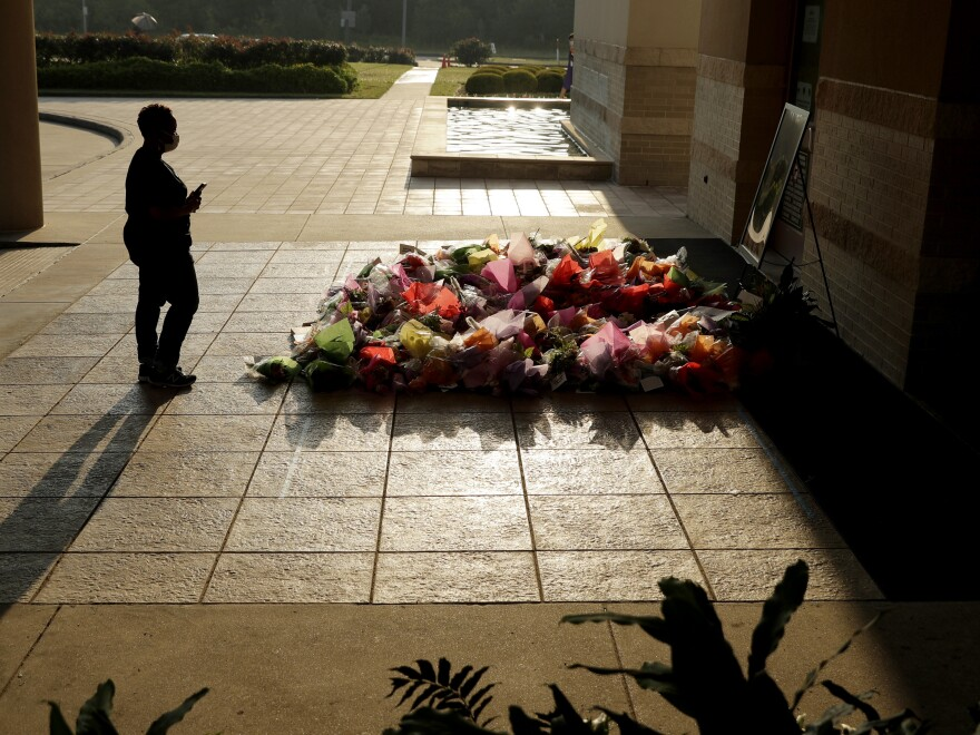 A woman stops to photograph a memorial Tuesday for Floyd at The Fountain of Praise church in Houston.
