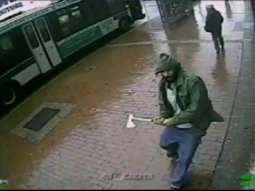 In this frame grab taken from video provided by the New York Police Department, an unidentified man approaches New York City police officers with a hatchet Thursday. The man was fatally shot by police after he wounded two officers.