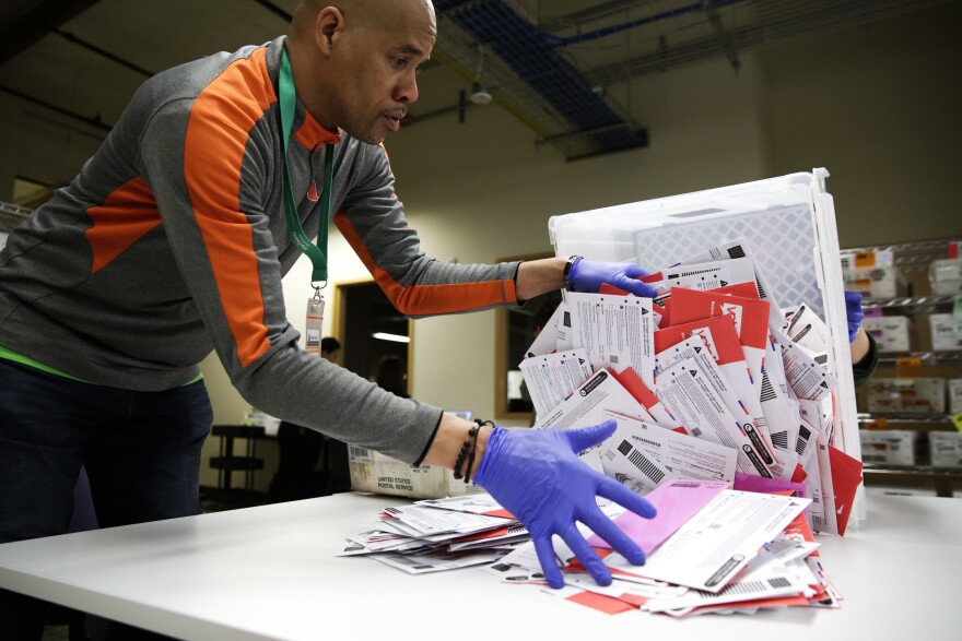 An election worker in Renton, Wash., begins processing mail-in ballots during that state's presidential primary in March. Varying state-by-state requirements around signatures and other rules have become the focus of legal fights as absentee voting expands due to the pandemic.