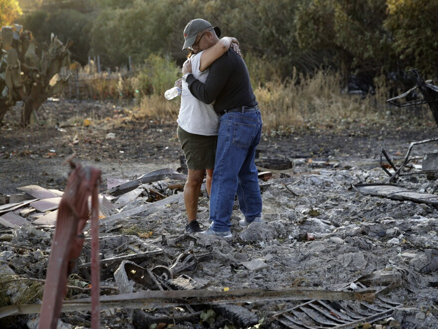 Justo and Bernadette Laos hug while looking through the charred remains of the home they rented that was destroyed by the Kincade Fire near Geyserville, Calif.