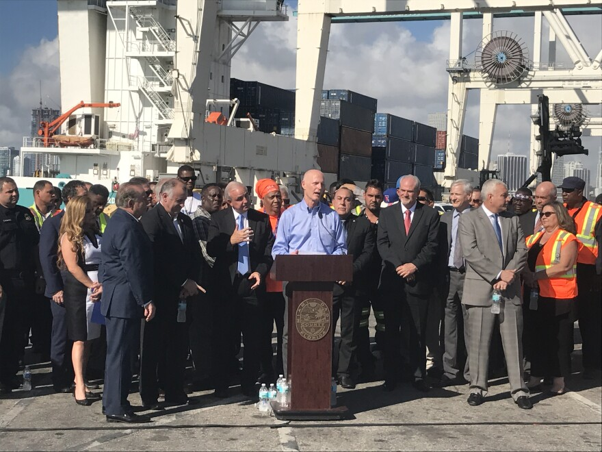 Port workers and local officials surrounded Florida Gov. Rick Scott as he touted job creation and transportation spending at PortMiami on Wednesday.