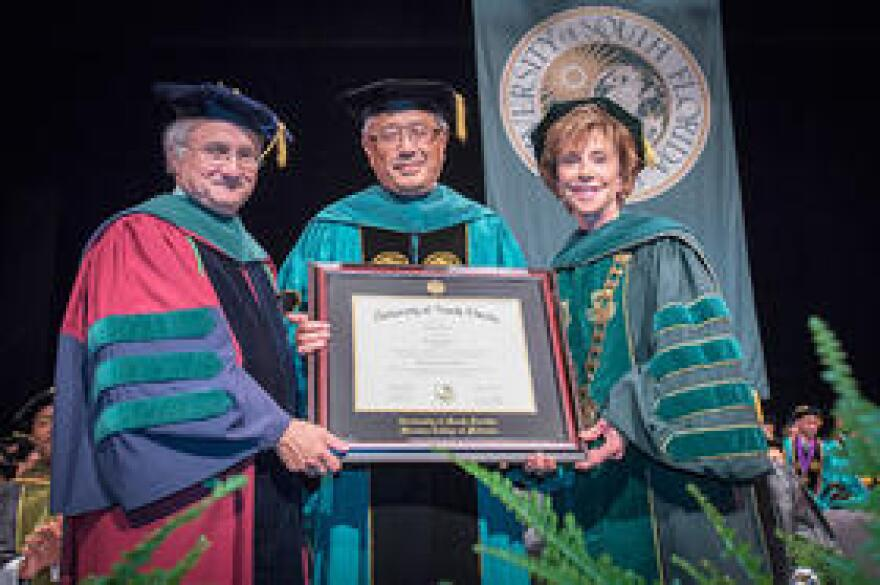 Dr. Victor J. Dzau, president of the National Academy of Medicine (center), receives an honorary degree from Dr. Charles Lockwood, Sr. VP of USF Health (left) and Judy Genshaft, President of the USF System.