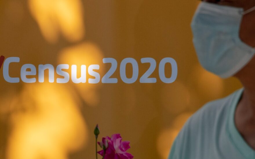 A man wearing a facemask walks past a sign encouraging people to complete the 2020 US Census, in Los Angeles, California amid the COVID-19 pandemic.