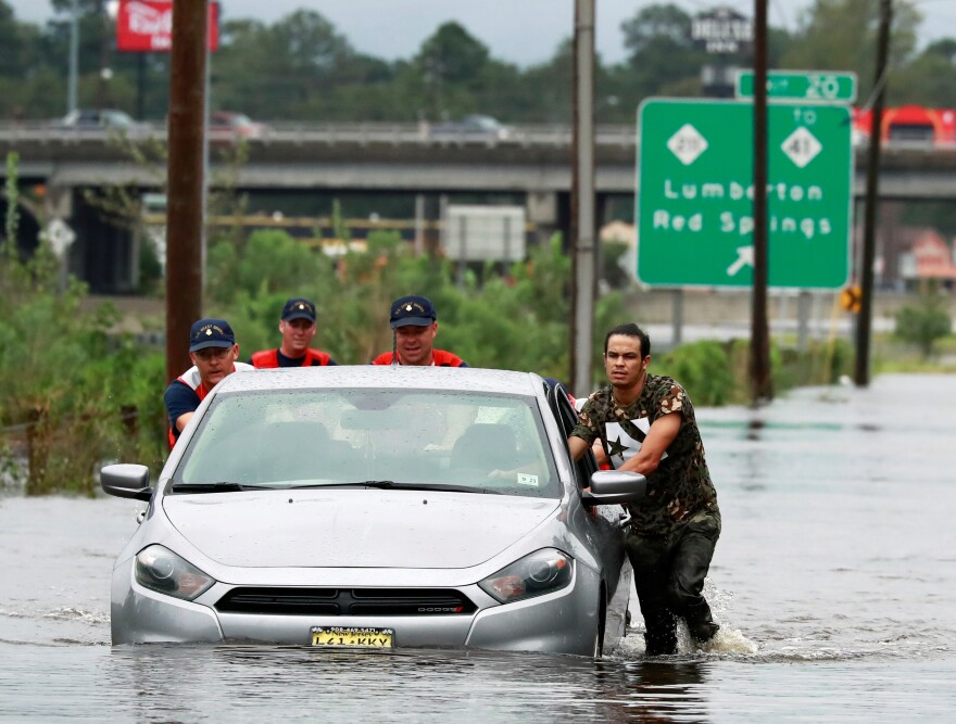 Three members of the Coast Guard help a stranded motorist Sunday in the flood waters caused by Florence in Lumberton, N.C.