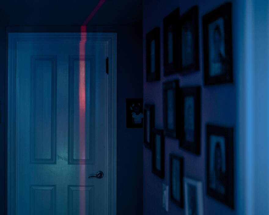 Red and blue hues spill onto Imma's bedroom door from her younger daughter's LED lights on May 10.