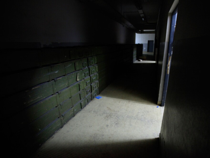 Boxes of weapons and ammunition line a hallway in the basement level of the presidential palace.