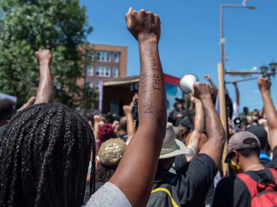 People raise their fists in a moment of silence for George Floyd in St. Paul, Minn., in July.