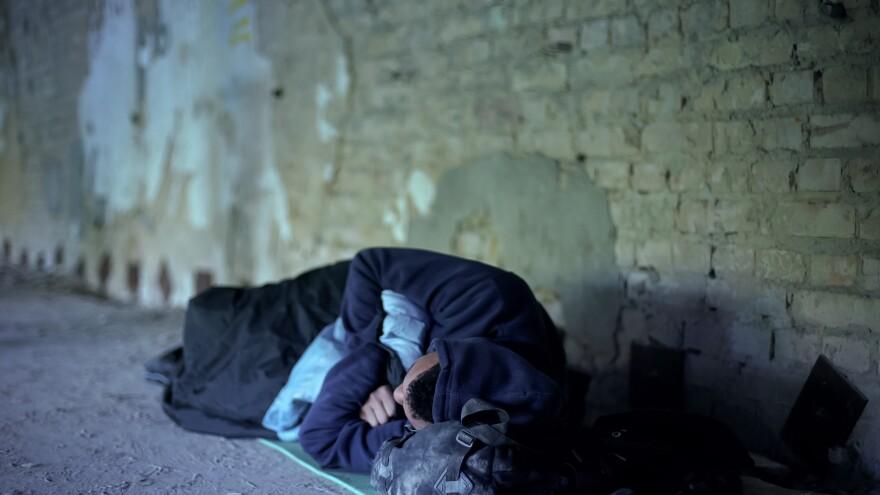 Homeless teenager sleeping on the street.