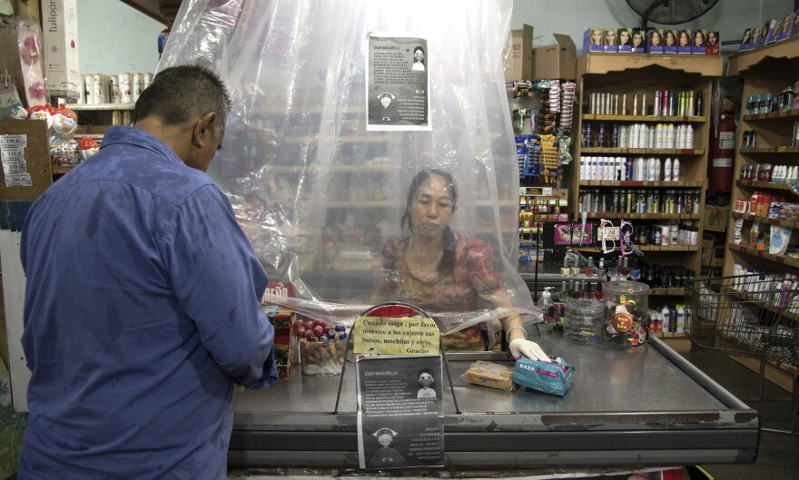 A cashier at a supermarket in Buenos Aires, Argentina, serves a customer from behind a makeshift plastic curtain intended to prevent the spread of COVID-19 on March 14.