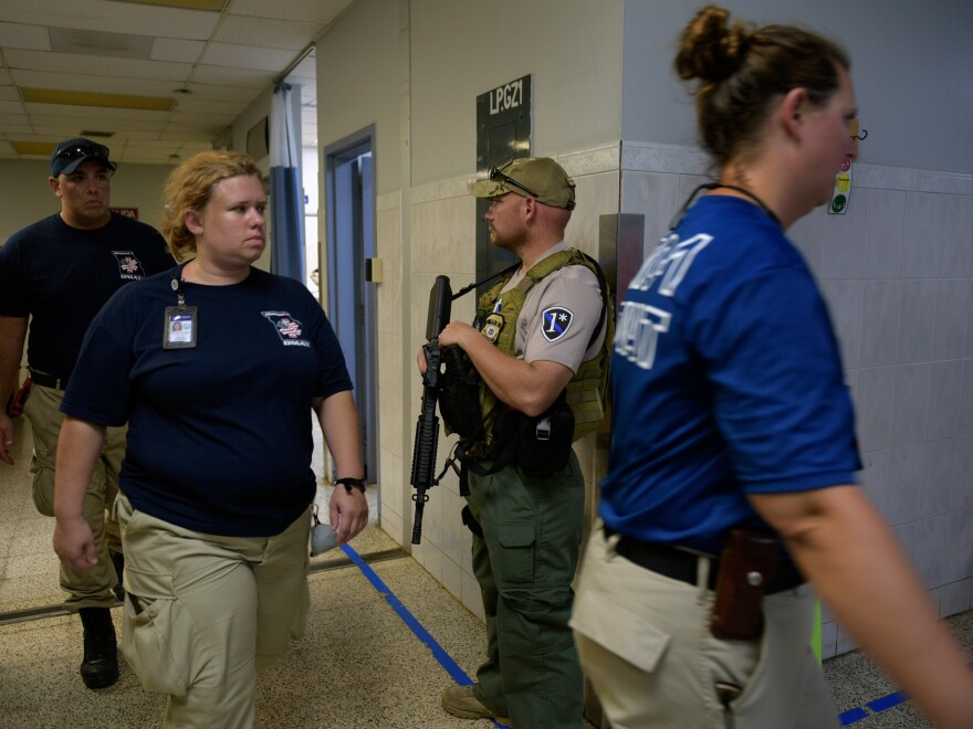 The U.S. Disaster Medical Assistance Team (DMAT) inspects a damaged hospital in Aguadillo, Puerto Rico, with a federal agent providing force protection.