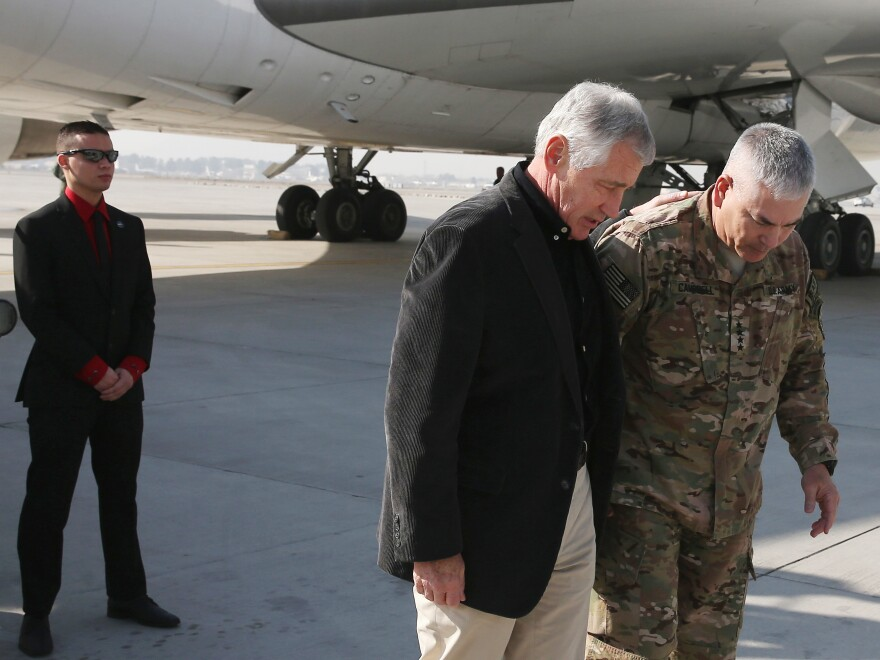 Secretary of Defense Chuck Hagel is greeted by Gen. John F. Campbell (right) after arriving in Kabul on Saturday. Hagel announced that an additional 1,000 U.S. troops would remain behind in the country after Dec. 31.