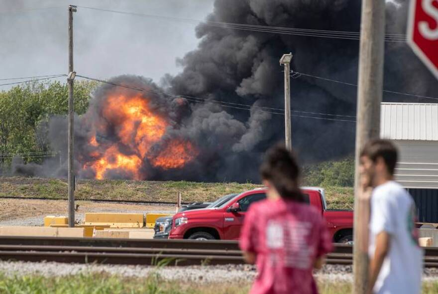 Onlookers stop in a parking lot across the from the fire in the Dupo train yard. Sept. 10, 2019