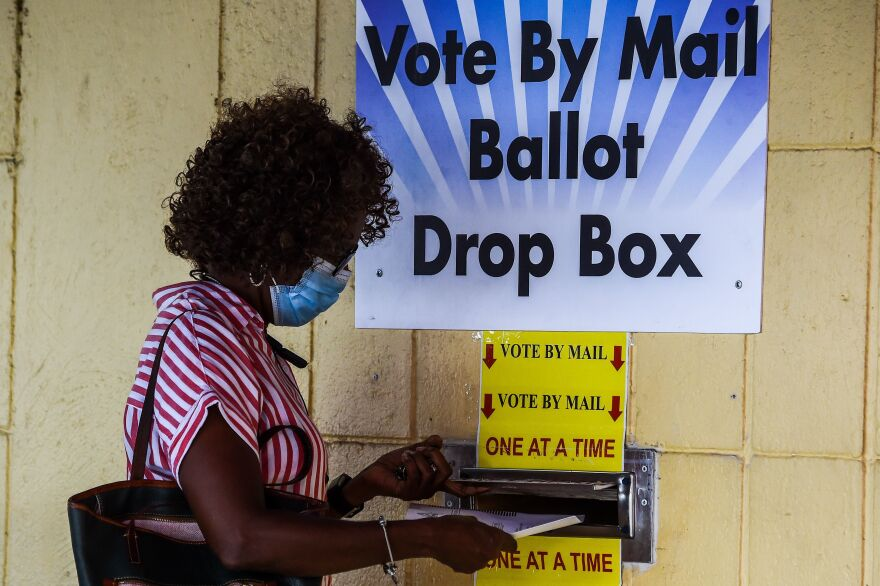 A woman drops her ballot by mail at Broward County Supervisor Of Elections Office in Lauderhill, Fla., on Oct. 5, 2020.