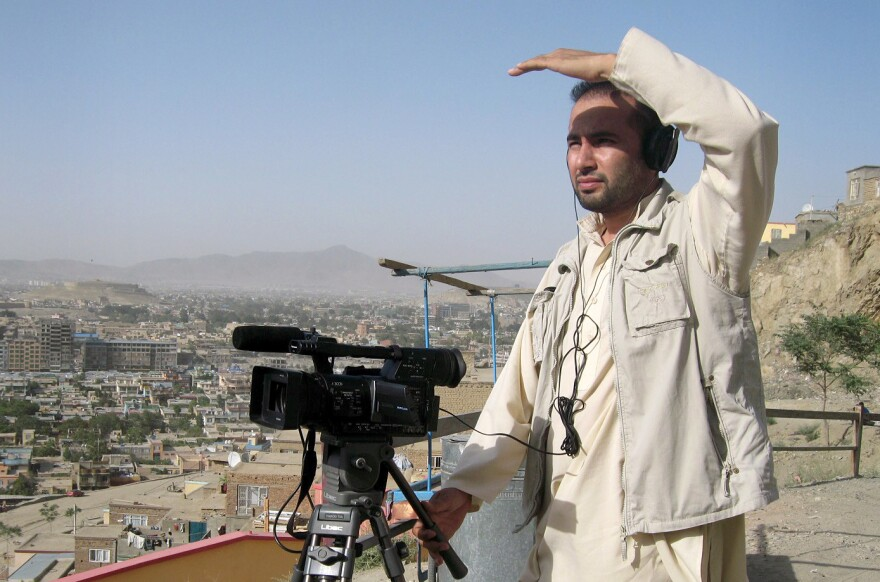 This July 2011 photograph shows Zabihullah Tamanna as he films a report on the outskirts of Kabul.