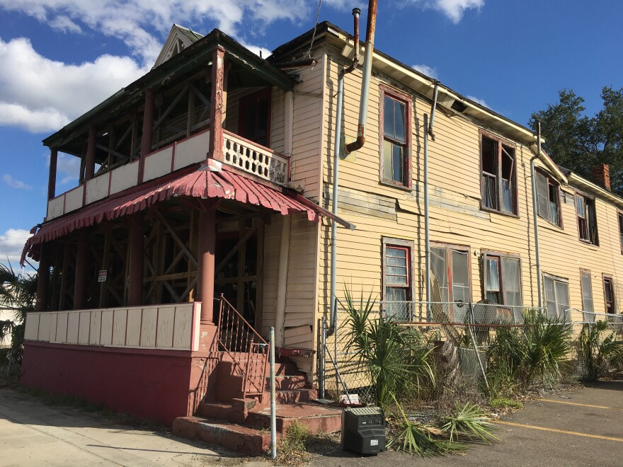 The Jackson Rooming House in Tampa is two stories, with peeling yellow and red paint. It's looks like it's falling apart.