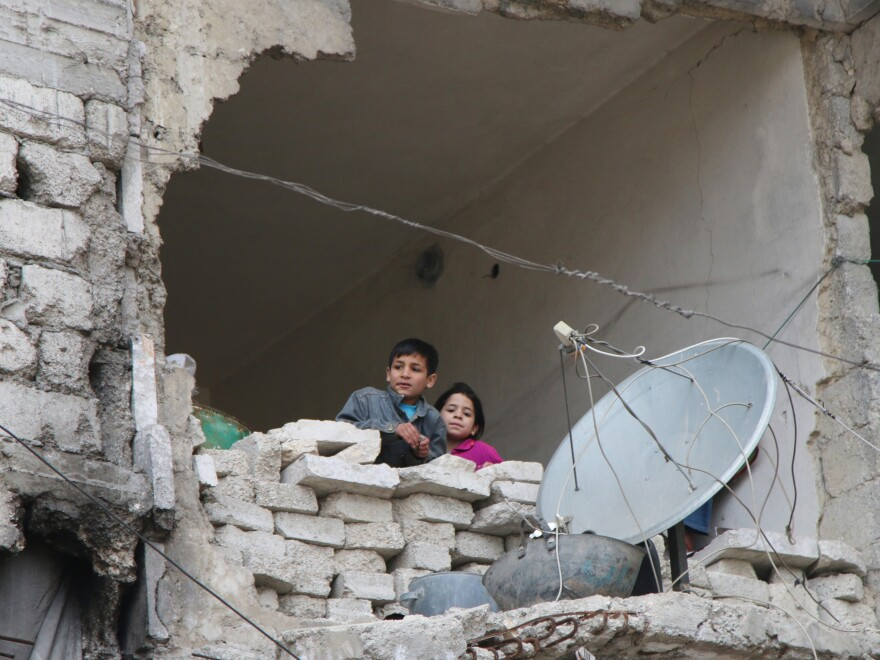 In this photo taken February 2016, children peer from a partially destroyed home in Aleppo, Syria.
