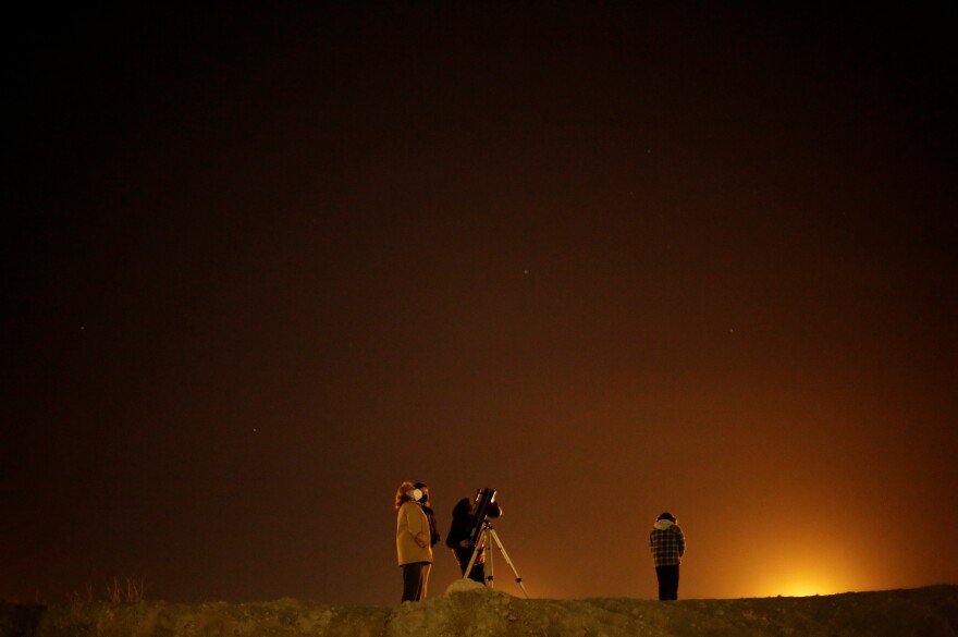 The family Mota Velazco, at the border crossing between Mexico and the United States in Ciudad Juarez, uses a telescope to view Jupiter and Saturn during the Great Conjunction.