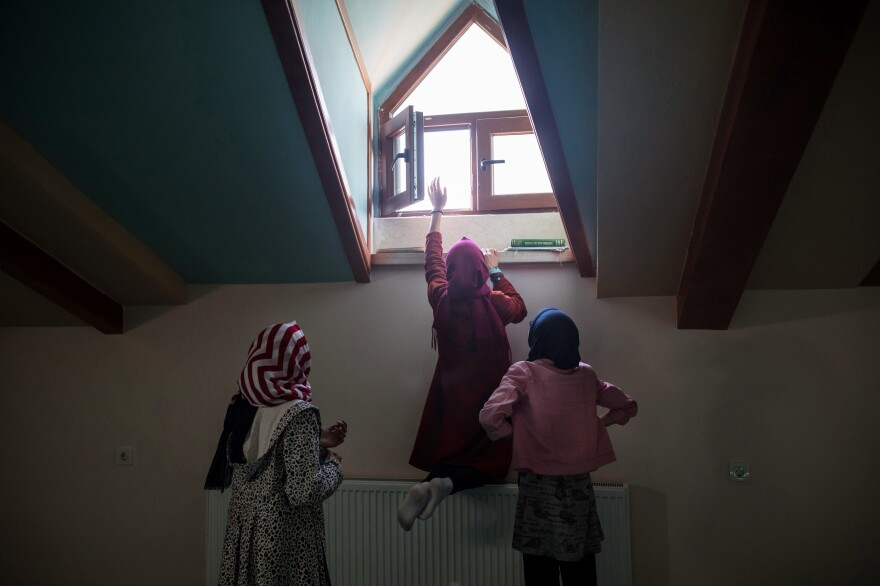 A student opens a window inside the school's mosque before the start of afternoon prayers. The school was built in 2017 and originally was expected to be a private institution where parents would pay tuition. The school's founders changed its mission after they noticed increasing numbers of Uighur children were stranded in Turkey without their parents.