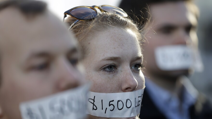 Silent protesters Wednesday in Lansing, Mich., wear tape with messages that signify wages they say they could lose because of the state's new right-to-work law.