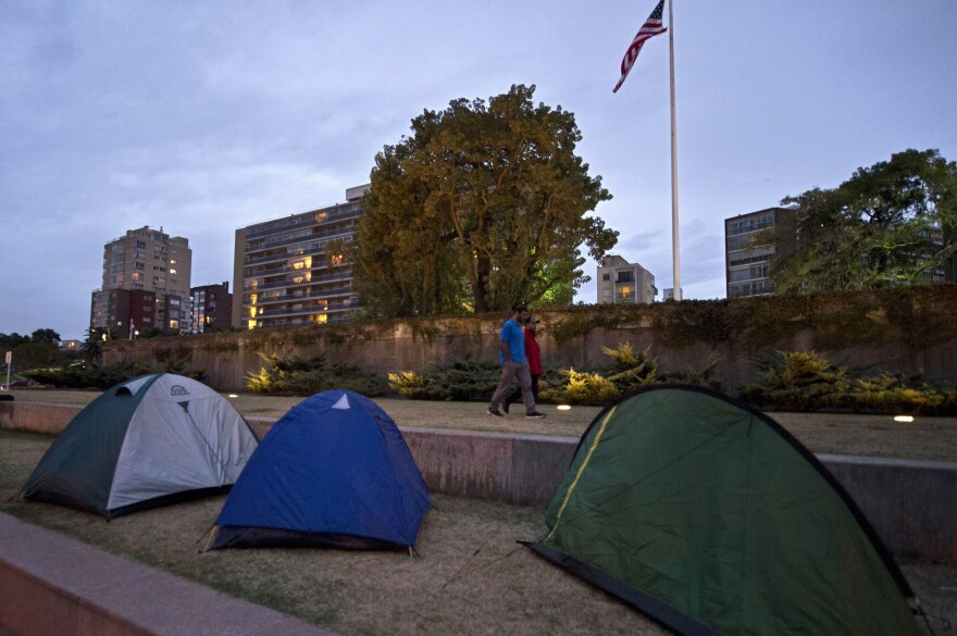 Former Guantanamo prison inmates walk between their tents and the U.S. Embassy in Montevideo, Uruguay's capital, where four former prisoners are protesting what they say is an inadequate deal in exchange for permanent asylum.