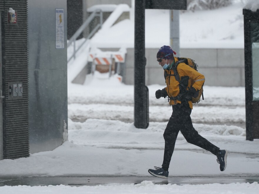 A person runs in the snow on Saturday on the University of Washington campus in Seattle. Winter weather was expected to continue through the weekend in the region. Winter conditions are forecast to extend through much of the U.S. early into the week.
