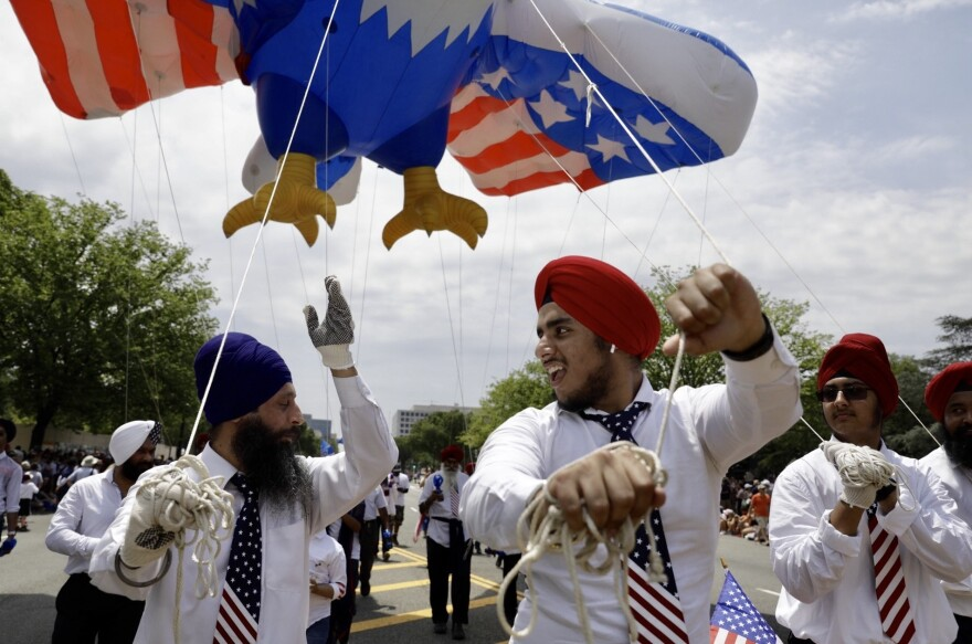 Men celebrate while holding onto a red, white and blue eagle balloon overhead during the National Independence Day Parade.