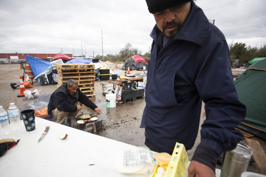Edward R. Ybarra (left) and Rafael Salazar (right), who are currently experiencing homelessness, prepare food over a fire at a state-sanctioned encampment in the Montopolis neighborhood for people experiencing homelessness.