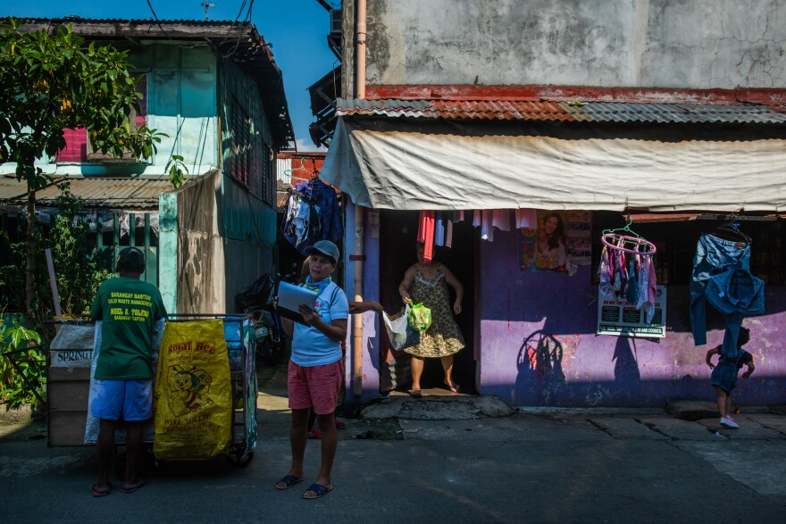 """The Baritan neighborhood in Malabon city has adopted a """"zero waste"""" policy that requires citizens to sort their trash and separate out the plastic. Above, trash collectors at work."""