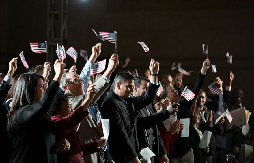 Group of immigrants waiving small United States flags.