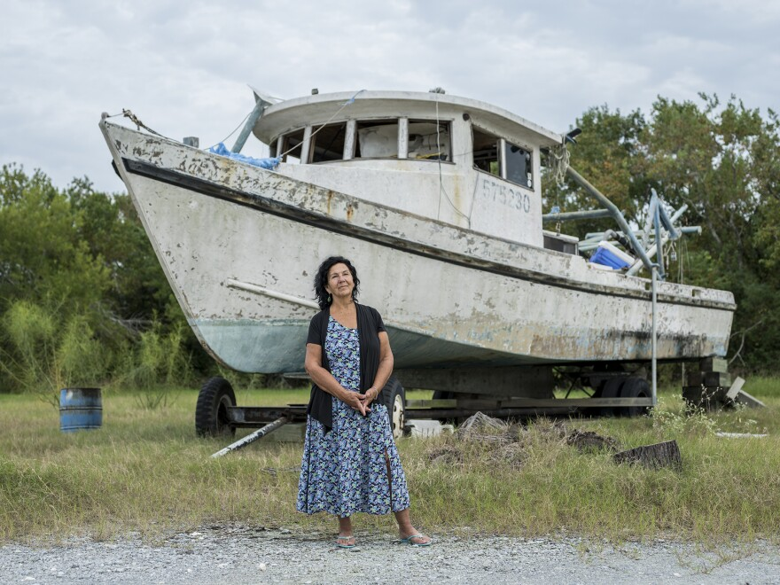 Diane Wilson, an outspoken native of Seadrift and a fourth-generation fisherwoman, stands by a retired shrimp boat.