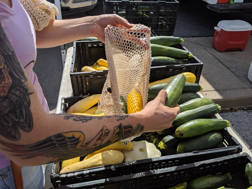 An Old Town Farmers Market visitor places fresh zucchini in a bag on July 20.