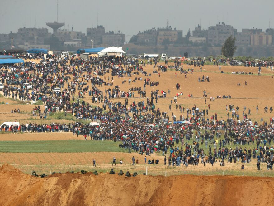 """From the southern Israeli kibbutz of Nahal Oz, Palestinians can be seen participating in the """"March of Return"""" protests, under the alert eyes of Israeli soldiers, in the foreground."""