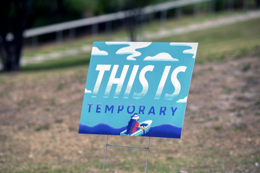a blue yard sign that says this is temporary.