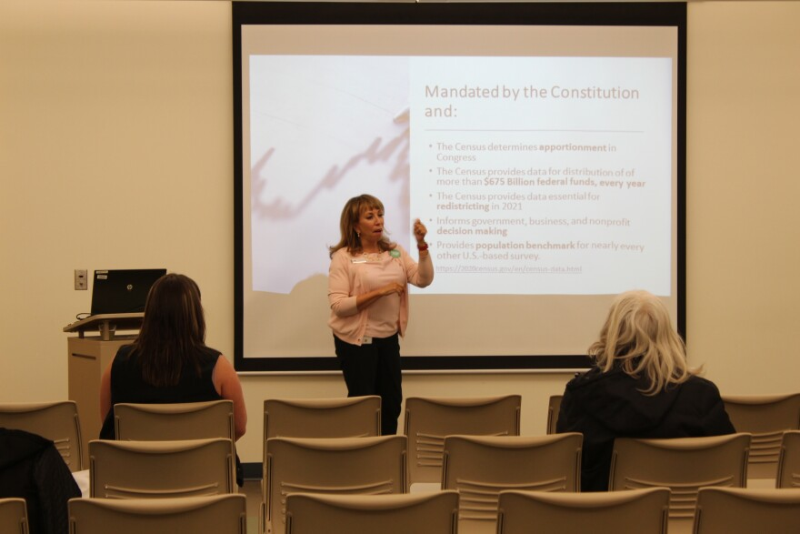 """A census worker gives a presentation to a small, sparse crowd in Sterling, Colorado's public library.  The PowerPoint Slide behind her reads """"Mandated by the Constitution and:"""" followed by six bullet points about why the census matters."""
