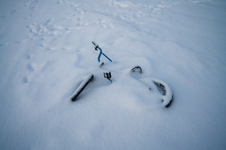 A children's bicycle lays in snow from a recent winter storm.
