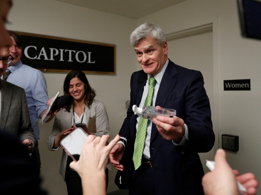 Sen. Bill Cassidy, R-La., gives news reporters hand sanitizer following a Senate hearing on the coronavirus on Capitol Hill Tuesday.