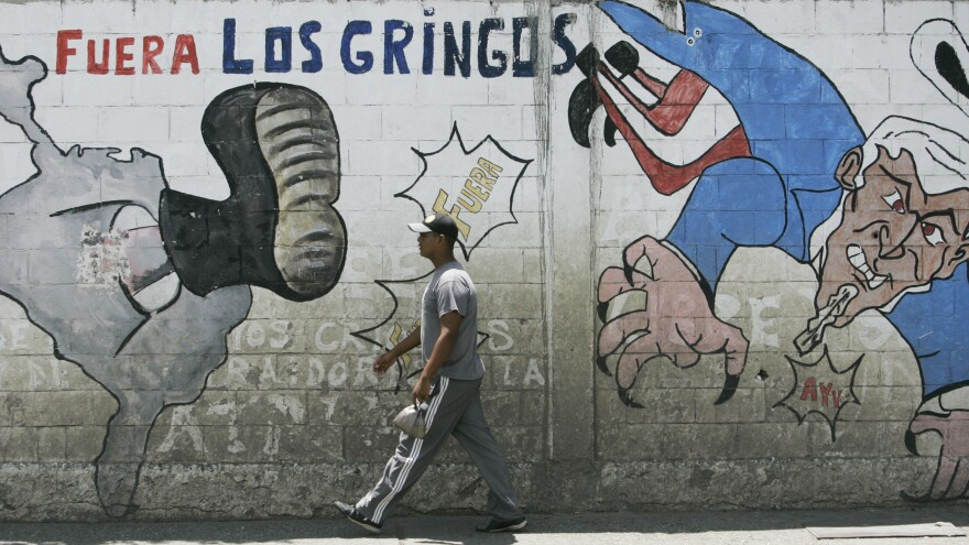 "A man walks past anti-U.S. graffiti that reads ""Gringos out"" in Spanish."