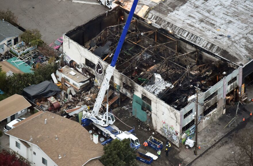 A crane is used to lift wreckage on Monday as part of search efforts in a fire-ravaged warehouse in Oakland, California. The death toll from the massive weekend fire at an artists' collective stands at 36, authorities say.
