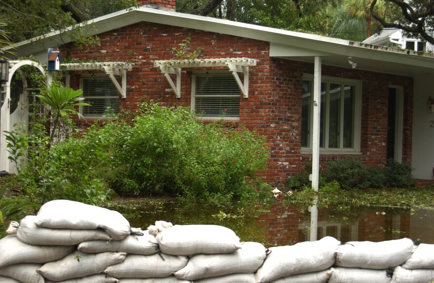 A house in Pinellas County during a flooding event, with piles of sandbags trying to protect it