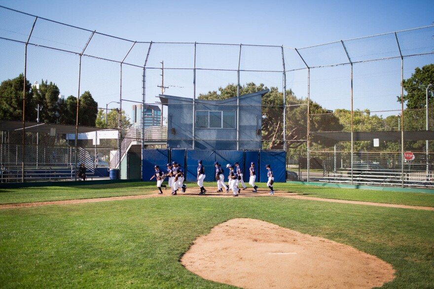 Ten-year-old Jake Herrera and his Los Angeles team run around the diamond as a warmup for baseball practice.