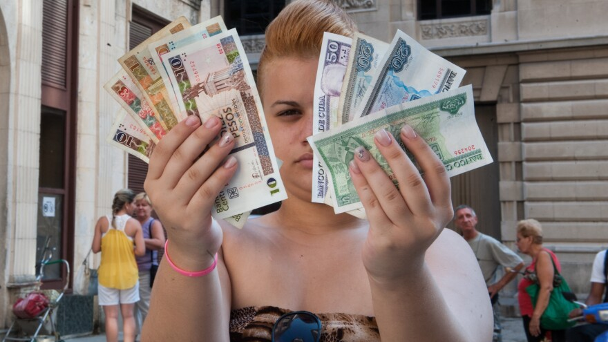 A woman displays Cuban pesos, or CUP (right) and the more valuable convertible pesos, or CUC (left), in Havana Tuesday. Raul Castro's government announced that it will begin unifying the two currencies.