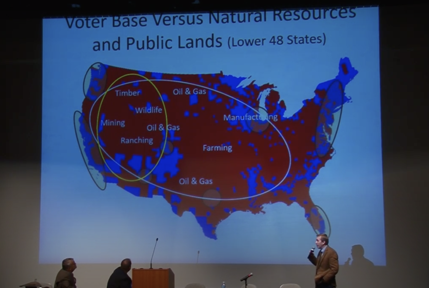 A powerpoint shows map color-coded in red and blue with circles around urban areas and natural resources