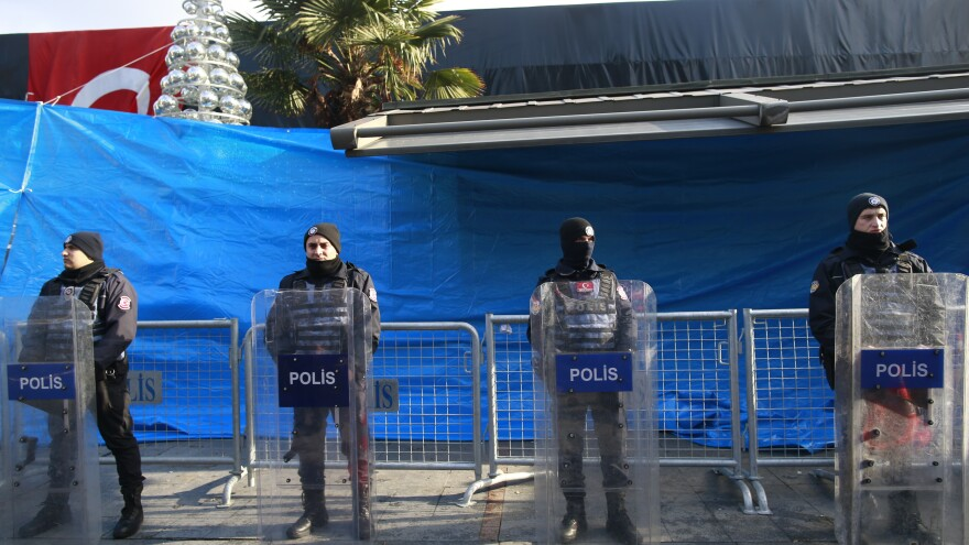 Turkish police officers stand guard outside an Istanbul nightclub that was attacked by a gunman on Sunday. Turkey's state-run news agency says that nearly two-thirds of the 39 people killed were foreign nationals.