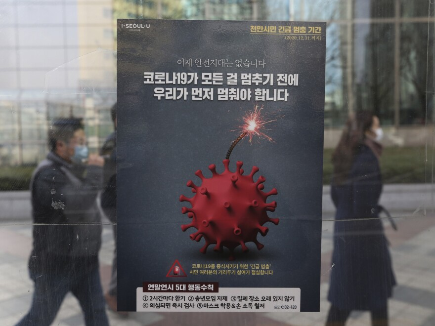 People wearing face masks as a precaution against the coronavirus pass by a poster emphasizing an enhanced social distancing campaign at a bus station on Monday in Seoul, South Korea.
