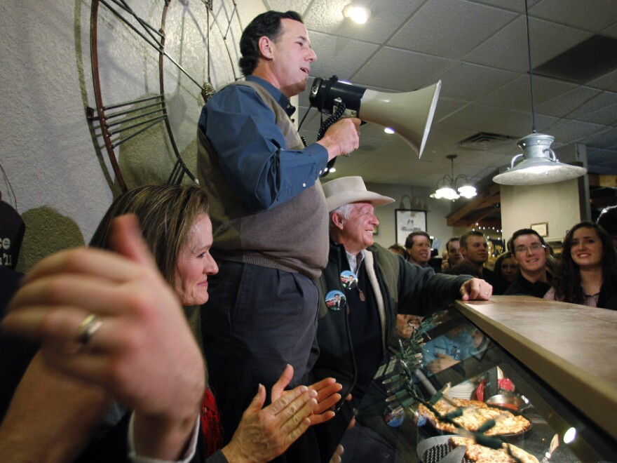 Former Pennsylvania Sen. Rick Santorum, who has recently surged in the Iowa polls, used a bullhorn during a meet-and-greet campaign stop Monday at the Pizza Ranch in Altoona, Iowa.