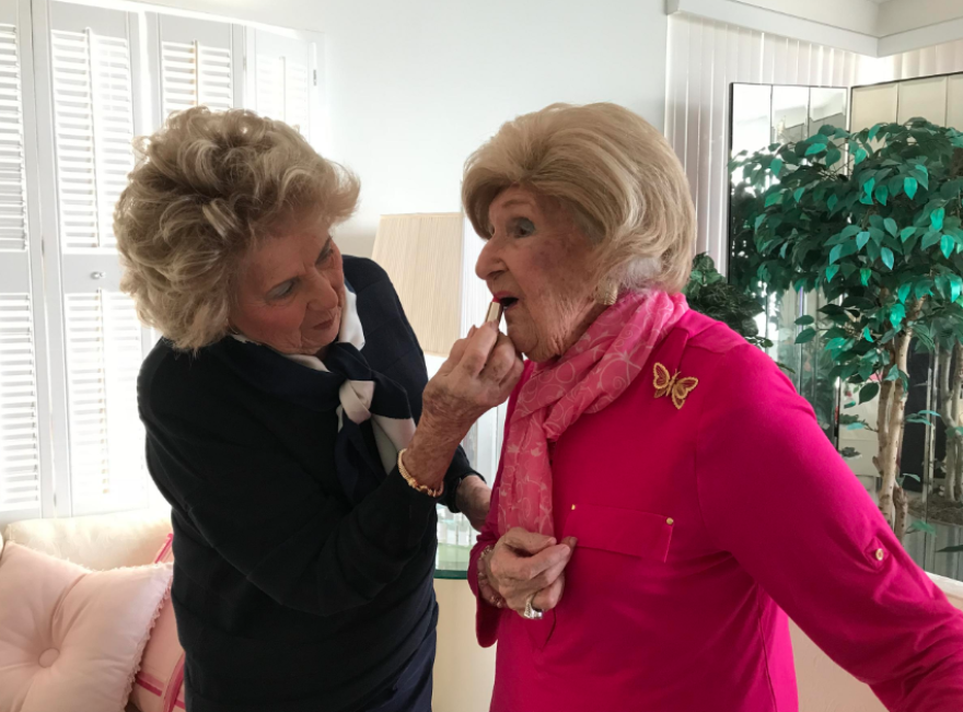 Johann Levinson (left), helps her mom, Mazie (right), put on her signature pink lipstick in 2017.