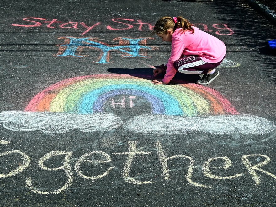 Girl makes chalk drawings on the driveway of their West Islip, New York.