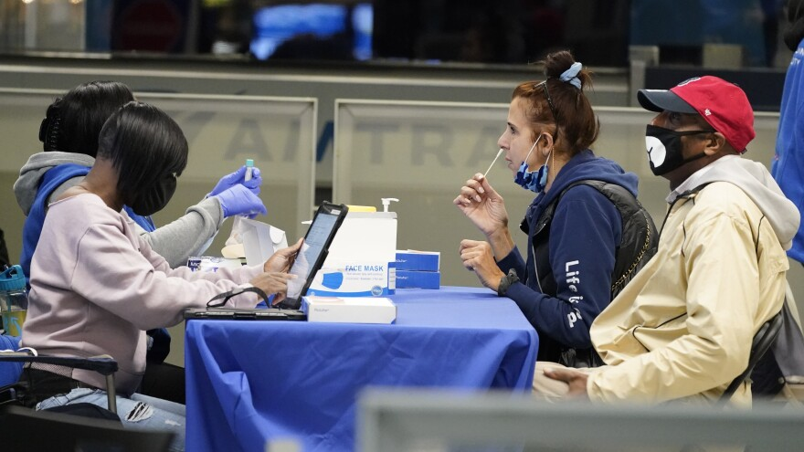 Travelers self test for COVID-19 at a mobile testing site at New York's Penn Station in the days leading up to Thanksgiving. The U.S. is currently seeing record hospitalizations for the virus, and health experts fear more surges are on their way.