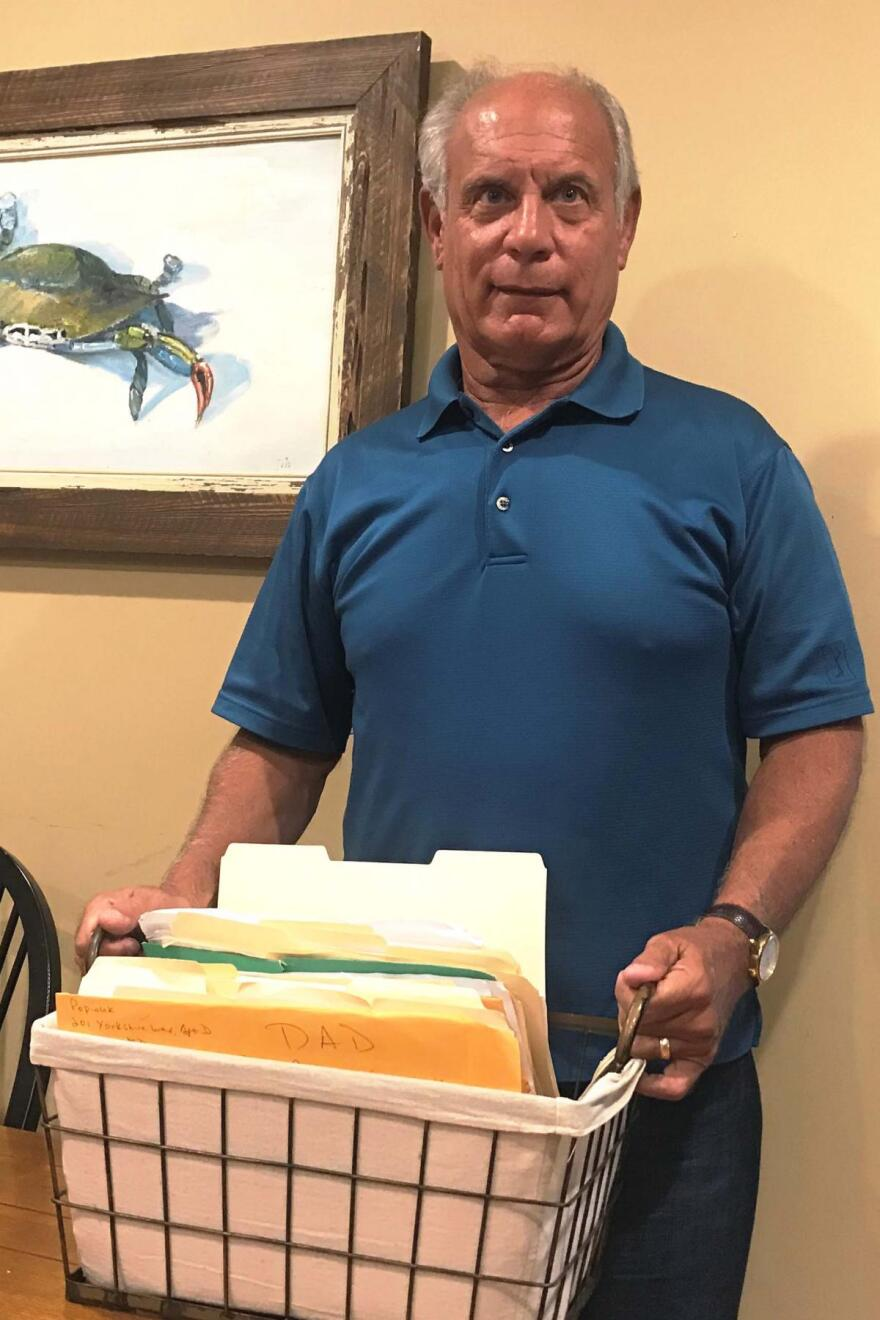 Gene Popiolek stands with the box of paperwork he keeps that documents his applications to get his dad Aid and Attendance.